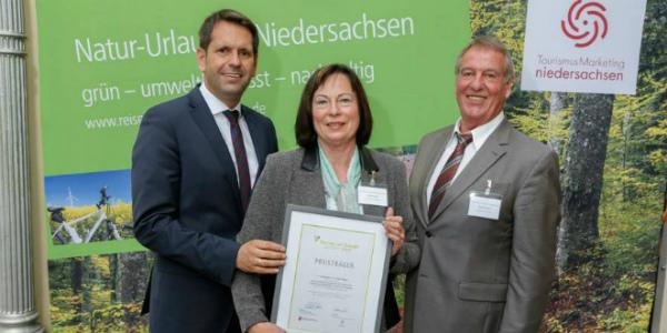 """Jutta Lesser (Mitte) mit der Urkunde des Wettbewerbs """"Tourismus mit Zukunft""""."""